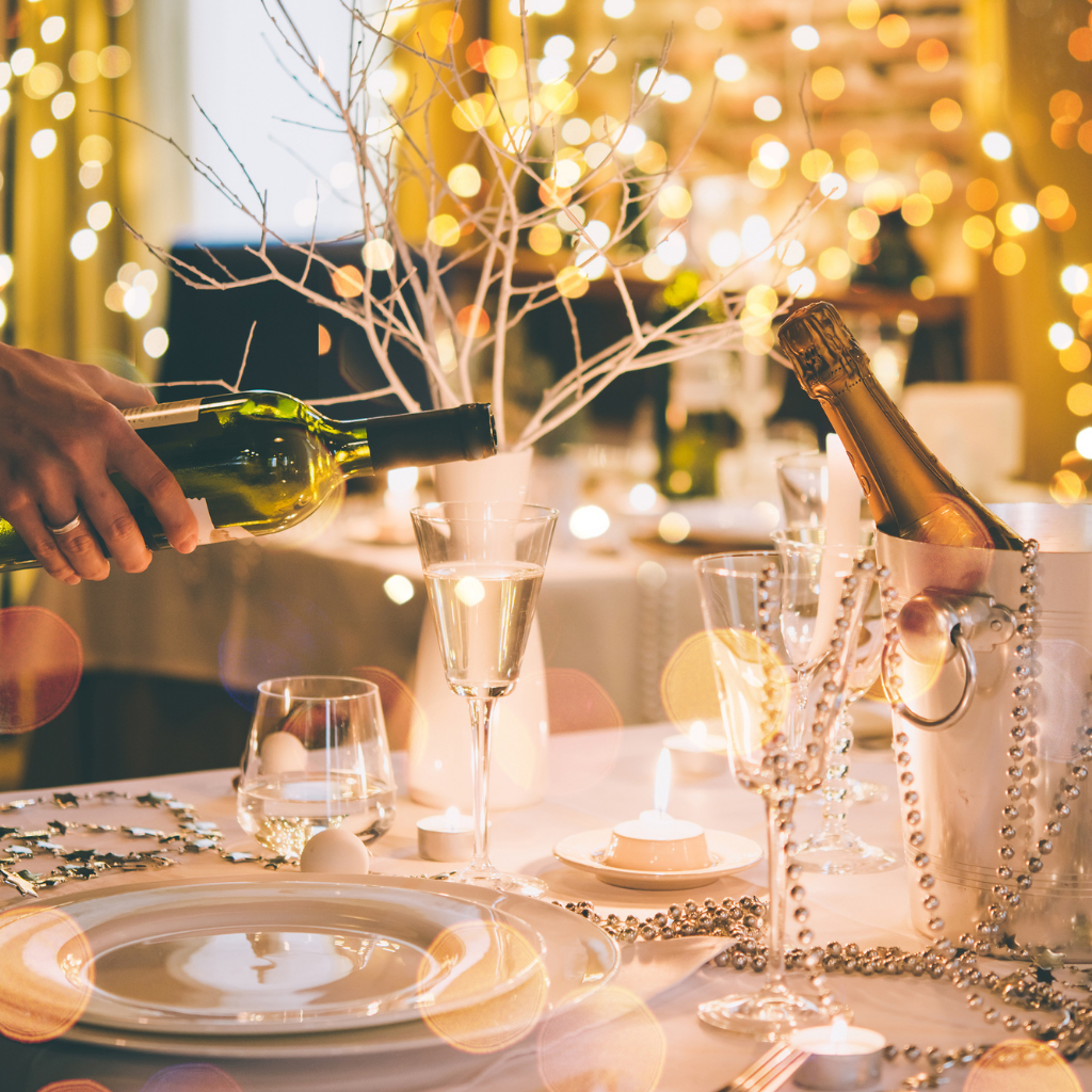 Table set for festive meal with champagne being poured into glass